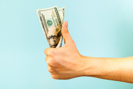 good investment: Money like hand on blue background
