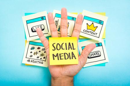 datos personales: Medios de comunicaci�n social en la mano con el fondo azul