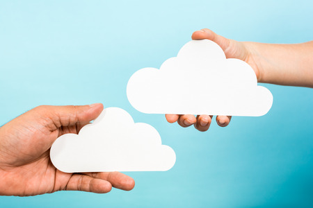 Two hands holding paper clouds on blue background.  Stock Photo