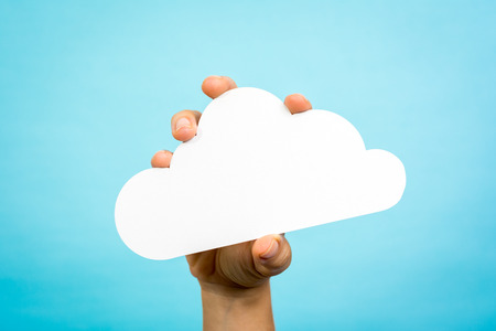 Woman hand holding a white paper cloud conceptual on blue background.