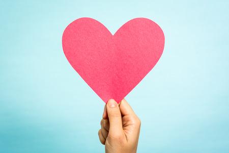 mujer enamorada: Mano que sostiene el amor de papel rojo forma de corazón sobre fondo azul.