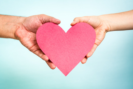 Two hands holding red paper love heart shape on blue background. Love concept. Archivio Fotografico