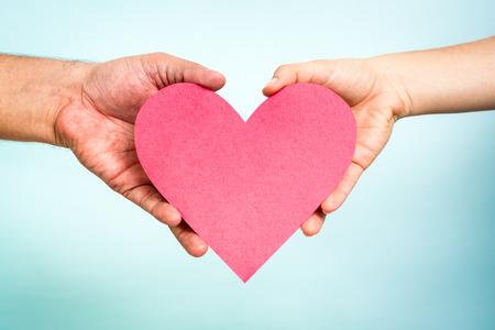 Due mani che tengono carta rosso amore a forma di cuore su sfondo blu. Concetto di amore. Archivio Fotografico - 35110099