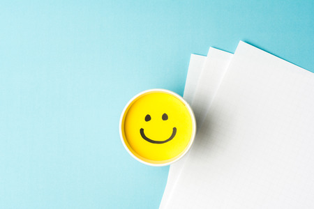Happy emoticonface and copy space on blue background and white papers
