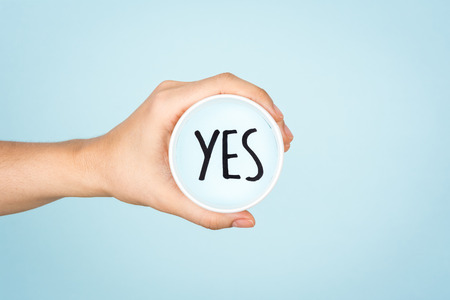 Yes text message concept. Hand showing a paper cup on blue background.