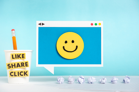 This digital marketing concept is showing speech bubble sign hanging with a happy face and to the left one paper mug with like, share and click labels and crumpled paper balls on desk. Stock Photo