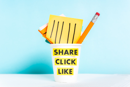 Share click like words. Paper cup with paper notes and pencil on blue background over desk.