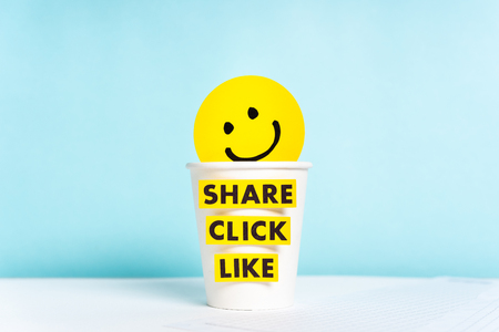 Social media concept with happy smiling yellow face over cup paper and share click like words, blue background.