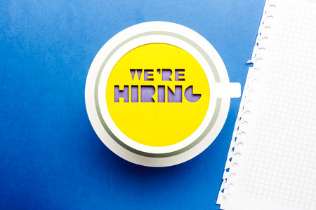 We are hiring concept. Yellow paper cup on blue background. Stock Photo