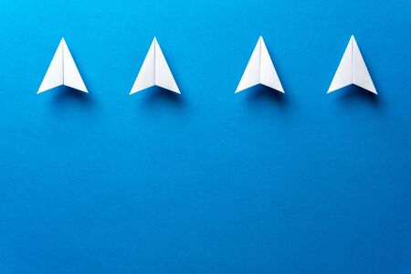 Four white paper airplanes, leadership, teamwork, motivation concept on blue background