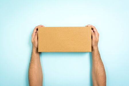 Concept of delivery and storage. Man showing a cardboard box with empty space. Only hands holding a closed box on blue background. Reklamní fotografie