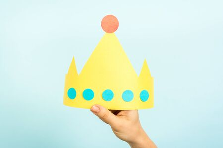 Concept of customer experience, best excellent services rating, satisfaction business, leadership and gender equality. Hand of woman holding a yellow crown.