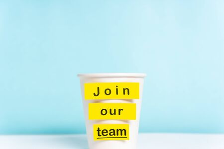 Concept of join our team or onboarding process. Paper cup with yellow top on desk with a paper cup over blue background. Stock Photo