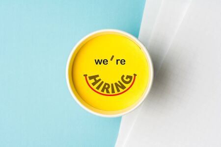 Concept of were hiring or join our team or onboarding process. Paper cup with yellow top on desk with blank documents over blue background. Stock Photo