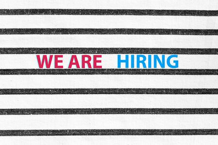 Concept of recruitment and job search. We are hiring red blue banner on black stripes and white textured background.