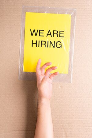 Hand raised trying to reach a classified ad. We are hiring printed on yellow paper on transparent plastic bag with cardboard background. Job aspirations, opportunity, search concept
