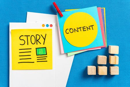 """Social media content sharing and digital marketing concept made with paper cards with the words illustrated """"story"""" and """"content"""" and wooden block toys on blue texture background."""
