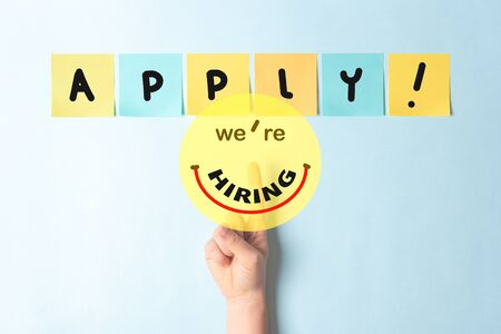 Job recruiting advertisement represented with a finger touching a button with text we are hiring simulating a happy smiling face. The word APPLY is written on multi colored notes with a blue background.