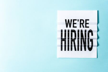 """""""We're hiring"""" lettering on textured blue background with blank or negative space. Job board design, template. Concept of recruiting for business."""