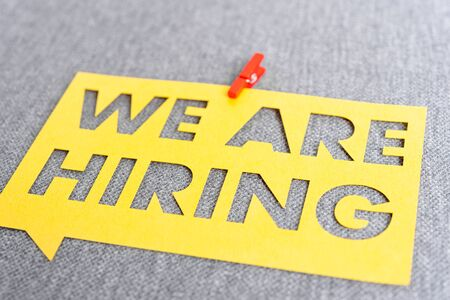 """""""WE ARE HIRING"""". Yellow speech bubble banner on blank gray textured background. Job search and employment concept"""