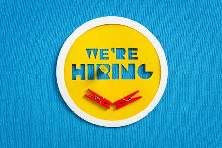 Happy we are hiring concept. Yellow button banner on blank blue textured background. Job search and employment concept with copy space.