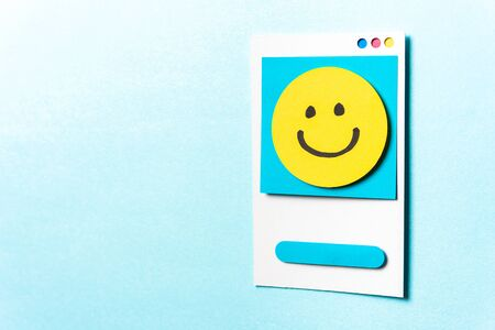Concept of well-being, well done, feedback, employee recognition award. Happy yellow smiling emoticon face paper card on blue background with empty space for text.