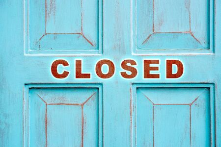 Concept of closed for maintenance or renovations or bankruptcy sign over vintage blue wood door background. Stock Photo