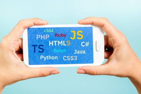 Concept of Programming banner signs, coding, programing languages. A woman hands showing the screen of paper smartphone on blue background.