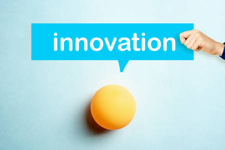 Concept of Innovation with a hand showing a speech bubble and yellow table tennis ball on blue background
