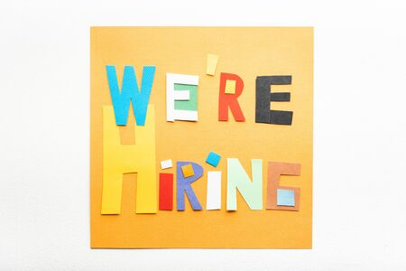 Recruitment concept. We are hiring banner sign made with cut paper on orange on the wall.