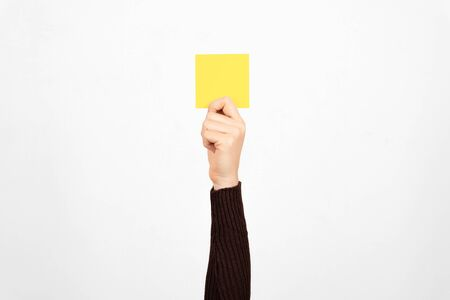 Hand of a business woman holding a yellow card in the air. Fault concept. Archivio Fotografico