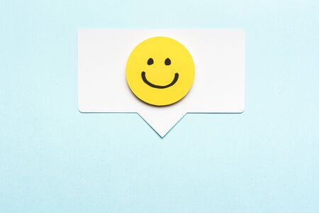 Happy face smiling comment on speech bubble and blue background. Stock Photo