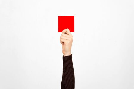 Hand of a business woman holding a red card in the air. Fault concept.