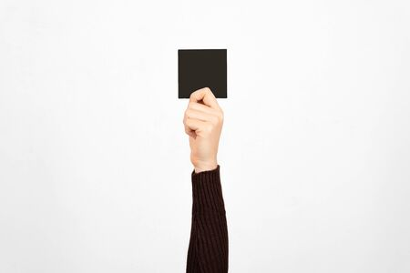 Hand of a business woman holding a black card in the air. Fault concept. Banco de Imagens