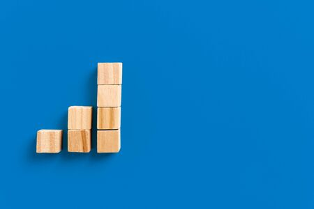 Growth bar chart, Graph diagram made with wooden block isolated on blue background and space for text. Business strategy, sales and marketing concept.