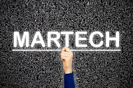 Woman showing MARTECH sign, on wire dark background. Martech is the blending of marketing and technology. Stock Photo