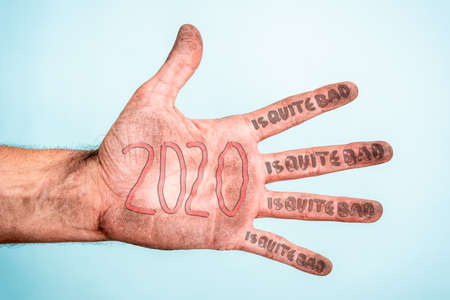 2020 is quite bad year, terrible worst year concept with a dirty hand and blue background. Bankruptcy, crisis, insolvency, stress concept.