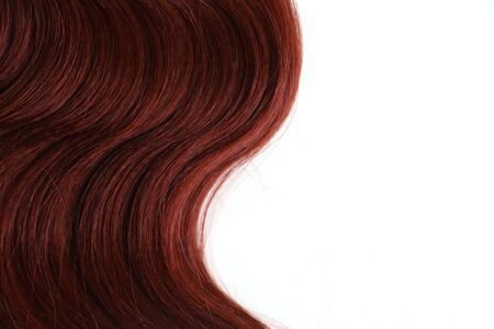 Isolated wavy auburn red hair piece with space for text