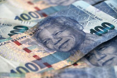 Nelson Mandelas face on the South African 100 rand bill pile of money currency