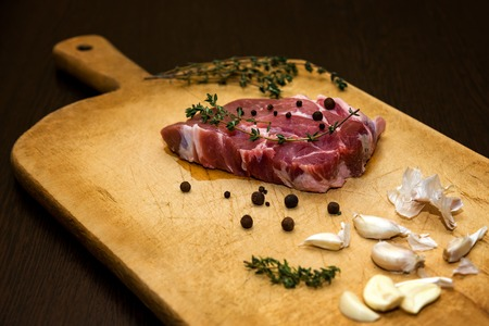 Raw marbled beef on a cutting board. On a black background