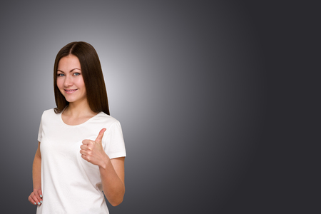 smiling faces: beautiful brunette girl with long hair and blue eyes showing thumbs up on gray background