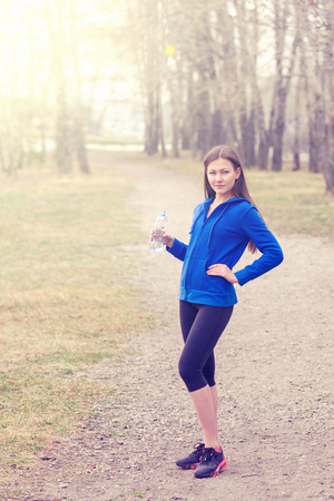 young woman with water bottle in hand before the run.a healthy way of life. sport fitness yoga Stock Photo