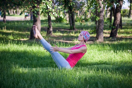 asana: young woman doing yoga and gymnastics in the park. boat pose Stock Photo