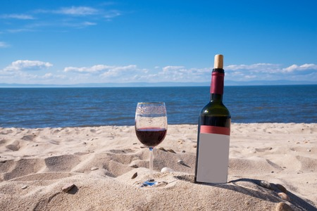 A glass of red wine and a bottle on the beach in a summer sunny day. Sea and blue sky in the background