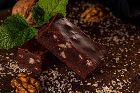 Homemade chocolate fudge with nuts on brown wooden background.
