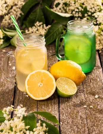 Homemade elderflower lemonade drink with lemon slice and mint in wooden background.