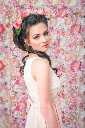 bridal hair: Beautiful woman wearing a bridal dress and flowers in her hair on flower background
