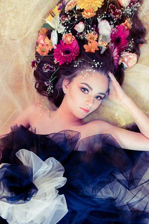 ojos verdes: Hermosa mujer rubia con grandes ojos verdes y flores en el pelo en el fondo de oro