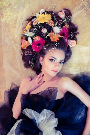 ojos verdes: Mujer rubia sensual con grandes ojos verdes y flores en el pelo que toca su cuello en el fondo de oro