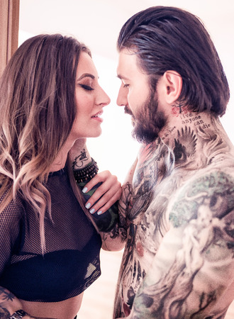 Sexy young tattooed man getting closer to kiss a sexy blonde woman indoors Stock Photo